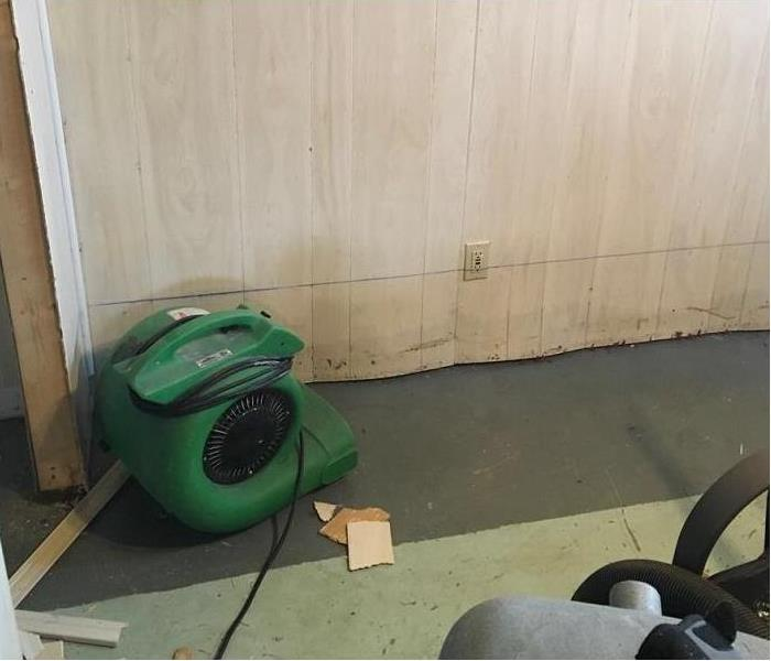 An air mover sitting in front of a wall with paneling.