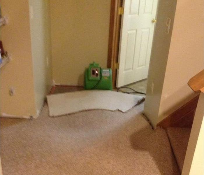 Hallway of a home with baseboards removed and carpet lifted with air mover set up under carpet.