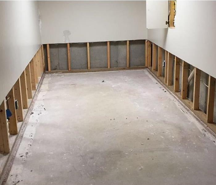 Room with white walls with lower portion of drywall and carpeting removed revealing cement floor and wall studs.
