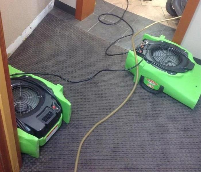 Hallway of a home with gray carpeting showing green SERVPRO air movers set up to dry the wet carpeting.