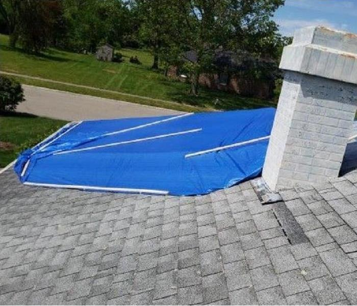 Roof of a home with section covered by blue tarp