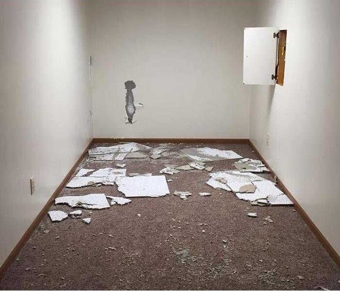 Room with white walls and carpeted flooring with debris scattered on the flooring.