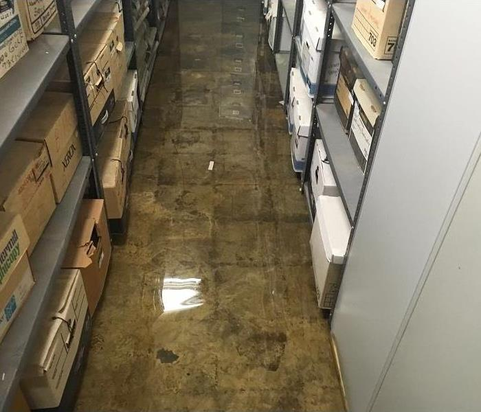 Warehouse with boxes on shelving and standing water on concrete floor.