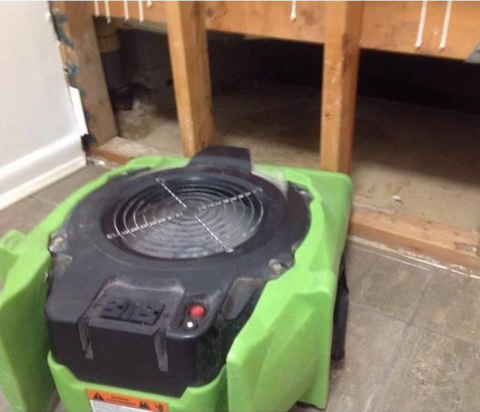 Green air mover machine sitting on floor pointed towards opened wall.